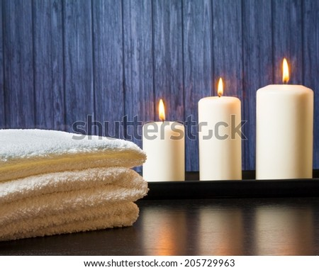 Spa massage border background with towel stacked and candles on wood background - stock photo
