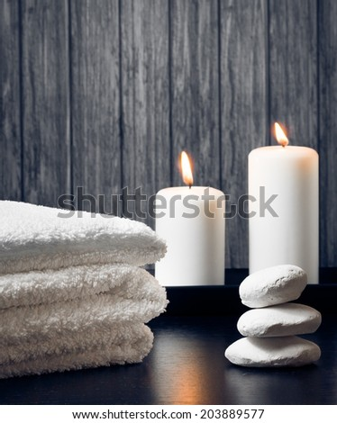 Spa massage border background with towel stacked,candles and stone on wood background - stock photo