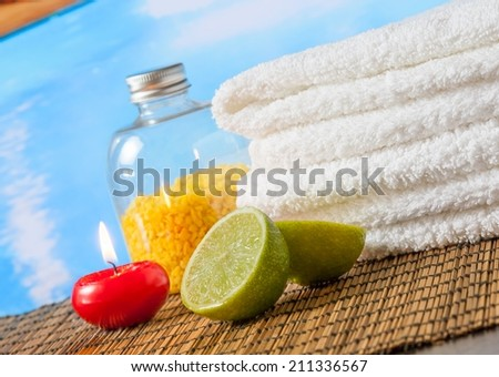 Spa massage border background with towel stacked,red candle and lime on swimming pool background - stock photo