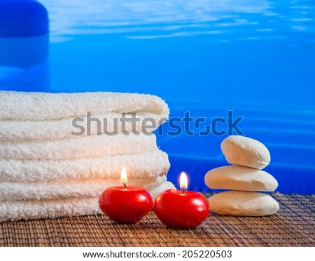 Spa massage border background with towel stacked,red candles and stone on swimming pool background - stock photo