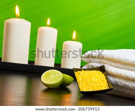 Spa massage border background with towel stacked sea salt candles and lime on green background - stock photo