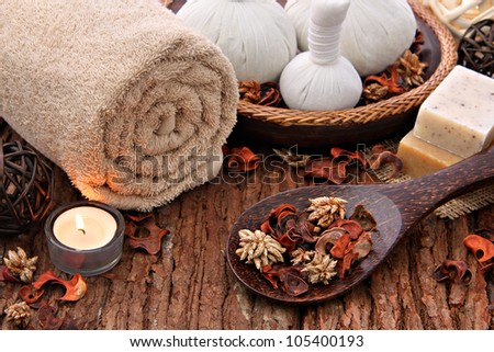 Spa massage setting with candlelight    Spa massage setting with thai herbal compress stamps and candlelight - stock photo