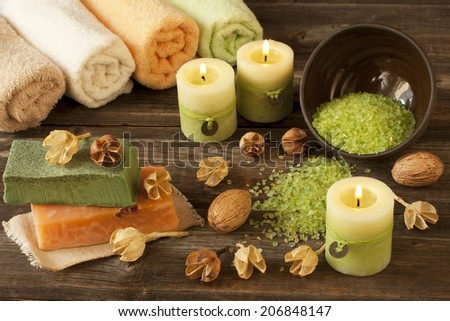Spa massage setting with rolls  towels,  natural soap and candlelight - stock photo