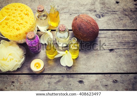Spa or wellness setting. Bottles with essential aroma oil, sea salt, coconuts and wisp on wooden background. Selective focus. Toned image. - stock photo
