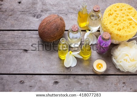 Spa or wellness setting. Bottles with essential aroma oil, sea salt, coconuts and wisp on wooden background. Selective focus. - stock photo