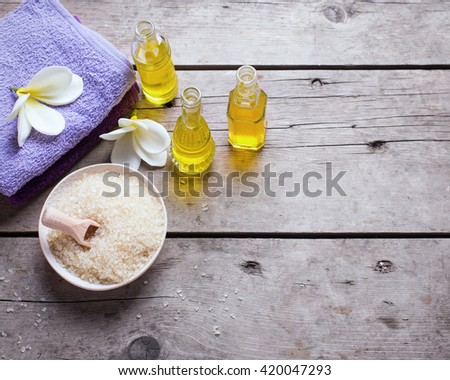 Spa or wellness setting in  yellow and violet colors. Bottles with essential aroma oil, towels, sea salt  on  aged wooden background. Selective focus. Place for text. Top view. Toned image. - stock photo