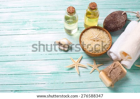 Spa or wellness setting. Sea salt in bowl, soap, aroma oil, pumice, towels and sea objects  on turquoise painted wooden planks. Selective focus is on sea salt. - stock photo