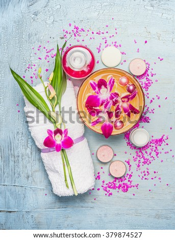 Spa or wellness setting with towel, bamboo leaves ,  bowl with pink orchid flowers and  water , cream, candles and sea salt on light blue  shabby  rustic background, top view - stock photo