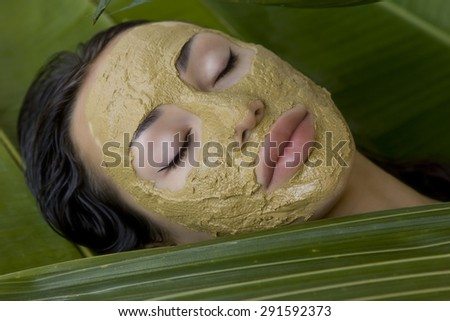 Spa Outdoor, Beautiful young woman lying with natural green herbal clay facial mask on her face, skin care and wellness - stock photo