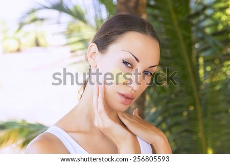 Spa Outdoor, Beautiful young woman lying with natural Indian Multani Matti clay facial mask on her face, skin care and wellness in tropical Thailand - stock photo