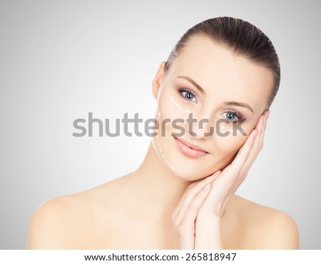Spa portrait of a young and healthy woman with arrows on her face. Plastic surgery concept. - stock photo