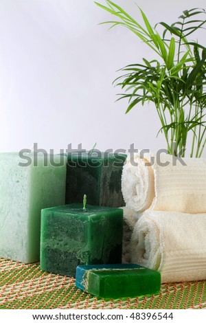 Spa products, candle, soap, towel and plant - stock photo