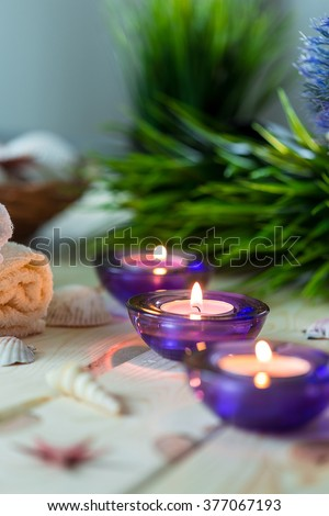 Spa Relax Set, Towels, Aromatic Candles in Purple Glass Candlesticks, Green Grass and Shells on Light Wooden Background, Vertical - stock photo