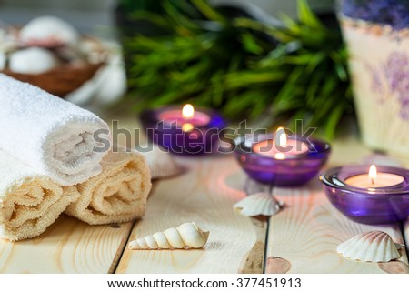 Spa Relax Set, Towels, Aromatic Candles in Purple Glass Candlesticks, Green Grass and Shells on Light Wooden Background - stock photo