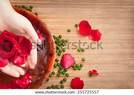 Spa Salon: Beautiful Female Hands with French Manicure in the Bamboo Bowl of Water with Red Roses and Rose Petals on the Straw Mat - stock photo
