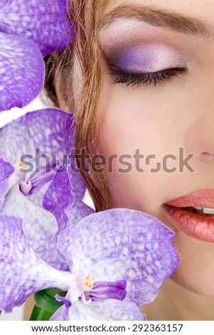 Spa salon: close-up of beautiful relaxing female face with violet orchids with professional make-up. Eyes closed. - stock photo