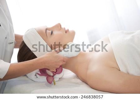 Spa salon: Young Beautiful Woman Having Facial Massage . - stock photo