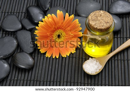 spa salt in spoon with gerbera and massage oil on pebbles on mat - stock photo