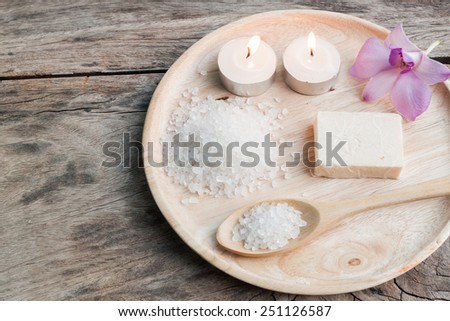 spa sea salt on wood plate with orchid ,wood background - stock photo