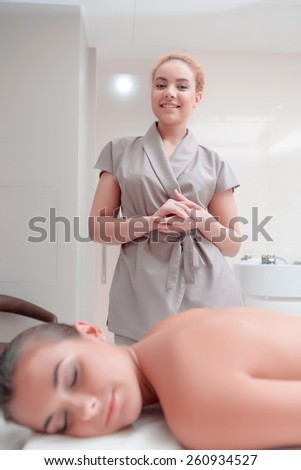 SPA serenity. Confident massage therapist ready for massaging beautiful young woman lying on massage table and keeping eyes closed with selective focus - stock photo