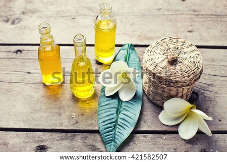 Spa set. Bottles with essential aroma oil and tropical flowers plumeria  on wooden background. Selective focus.Toned image. - stock photo