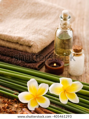 Spa set with flower, candle, oil on old wood - stock photo