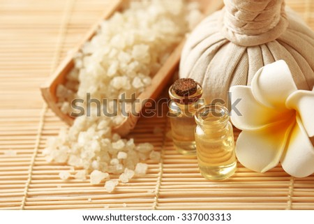 Spa set with massage balls, salt, aroma oil and frangipani flower on wicker background - stock photo