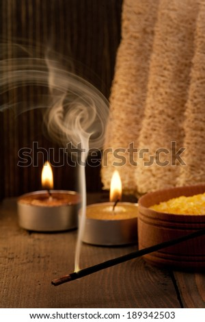Spa setting and fuming aroma stick on dark wooden background - stock photo