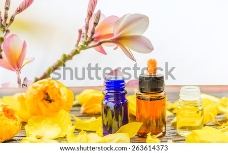 Spa setting, aroma essential oil and flowers on wooden in the blurry of flowers backgrounds soft focus. - stock photo