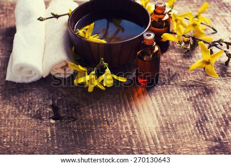 Spa setting. Essential aroma oil in bottles , water in bowl, towels, yellow flowers on aged wooden background. Selective focus. Place for text. Toned image.