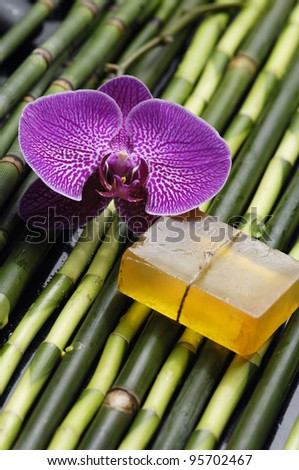 Spa setting -handmade natural Soap orchid on thin bamboo grove background - stock photo
