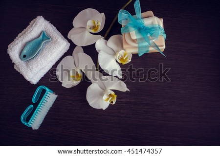 Spa setting in purple and blue colors with different kind of natural soaps, soft towels and orchid on dark wooden background. Tower stack of different handmade soaps. Selective focus. Copy space. - stock photo