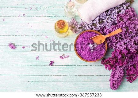 Spa setting. Natural sea salt, organic aroma oils, lilac flowers, towels on turquoise painted wooden planks. Selective focus. Place for text. Top view. - stock photo