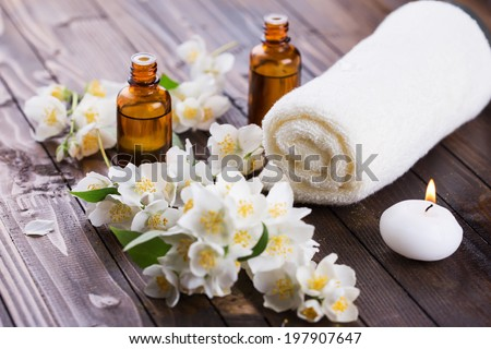 Spa setting on wooden background. Towel, aroma oil, candle, flowers. Selective focus, horizontal. - stock photo
