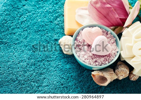 Spa setting with bath salt  and bath accessories on blue towel - stock photo