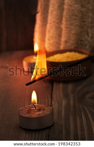 Spa setting with candle and burning aroma stick on dark wooden background - stock photo