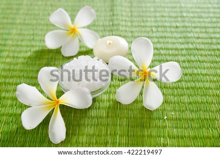 Spa setting with candle, salt in bowl with frangipani - stock photo