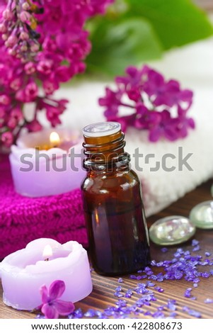 SPA setting with candles, aroma oil and lilac flowers - stock photo