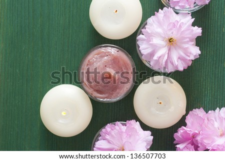 spa setting with cosmetics, candles and japanese cherry blossoms, wood table background - stock photo