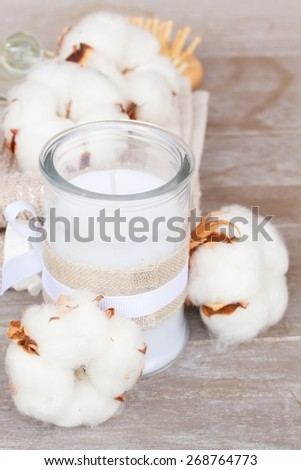 spa setting with cotton buds  and candle on gray table  - stock photo
