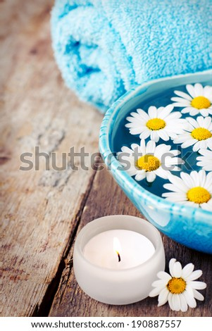 Spa setting with daisies in bowl on wooden background, toned - stock photo