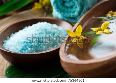 Spa setting with flower and towel on wooden background. - stock photo