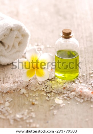 Spa setting with frangipani ,massage oil ,salt,towel - stock photo