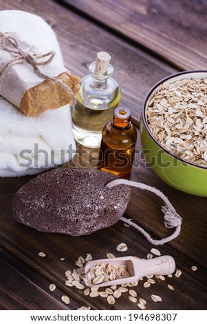 Spa setting with oat flakes on  wooden background. Soap, pumice, aroma oil. Selective focus, vertical. - stock photo