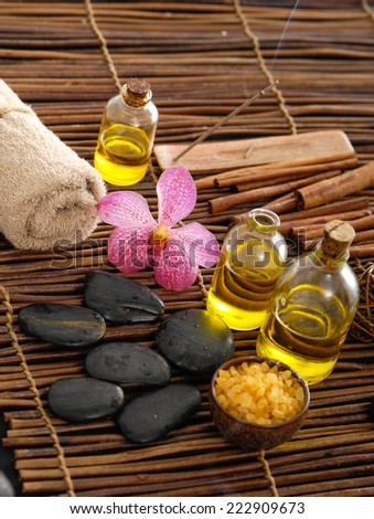 Spa setting with orchid and towel,black stones, oil , cinnamon, on mat  - stock photo
