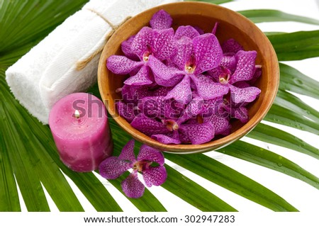Spa setting with orchid in bowl with towel, candle on green palm leaf - stock photo