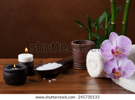 Spa setting with sea salt, candles, towels and orchids. - stock photo