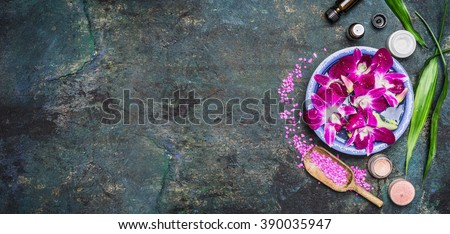 Spa setting with water bowls , pink orchid flowers ,sea salt, cosmetic cream and essential oil on dark rustic background , top view, place for text, horizontal, banner. Wellness concept - stock photo