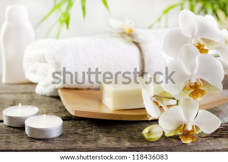 Spa soap orchids and towel on white background with palm - stock photo