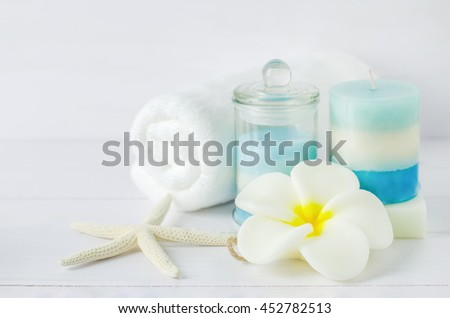 Spa soap with Plumeria flower shape and aromatherapy spa tools, towel, blue aroma spa salt, layered aroma spa candle, starfish on white wooden background - stock photo